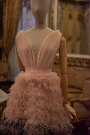Vestido largo en rosa y negro con escote en uve, tul y aplicaciones de plumas. Claro Fernando